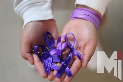 Junior Olivia Cerda holds ribbons in remembrance of Mackenzie Cowan. Cowan passed away on Sept. 27th, 2019, and students made 600 pins to honor her.