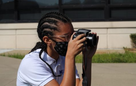 Sophomore MaryKathryn Wert takes photos with the newspaper staff.