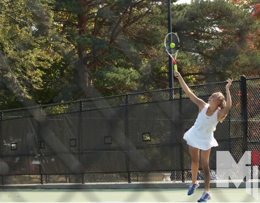 Senior Delaney Pepin goes up for a serve during her doubles match.