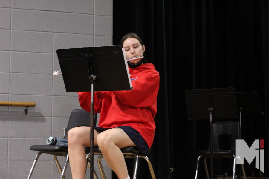 Eyes fixed on the music notes, senior Erin Garr practices her flute.
