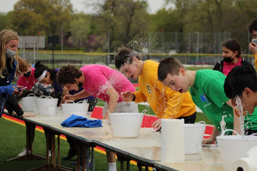 CHILL AND THRILL Embracing the ice water, one student from each herd participates in the bobbing for apples competition during herd day on April 23. Senior Leo Gajewski was the first to  successfully collect two apples and win the challenge.