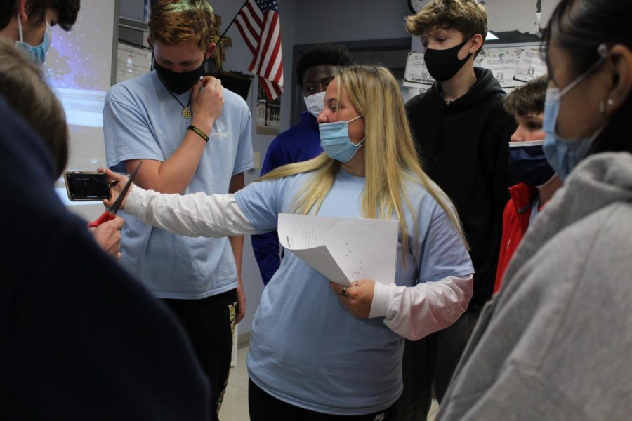 AGAINST THE CLOCK Reading the escape room tasks on the her phone, Perrini herd executive Olivia Hayward guides her faith family in the competition during herd day on April 23. This was the first competition of the day.