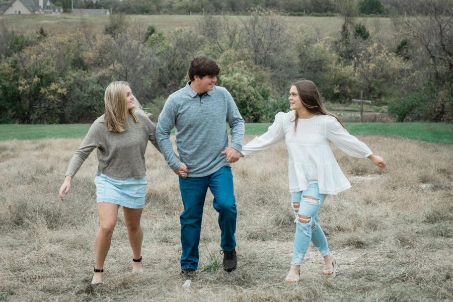 Senior Emma Werner walking hand in hand with sister, junior Ava, and brother, freshman Dominic.