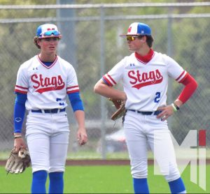 Standing together having a conversation between innings, Logan (left) and Luke (right) Shull wait to continue the team's consistent start to the season. Both brothers will be playing baseball at Washburn University as other members of the senior class head to 28 different colleges to play. |
