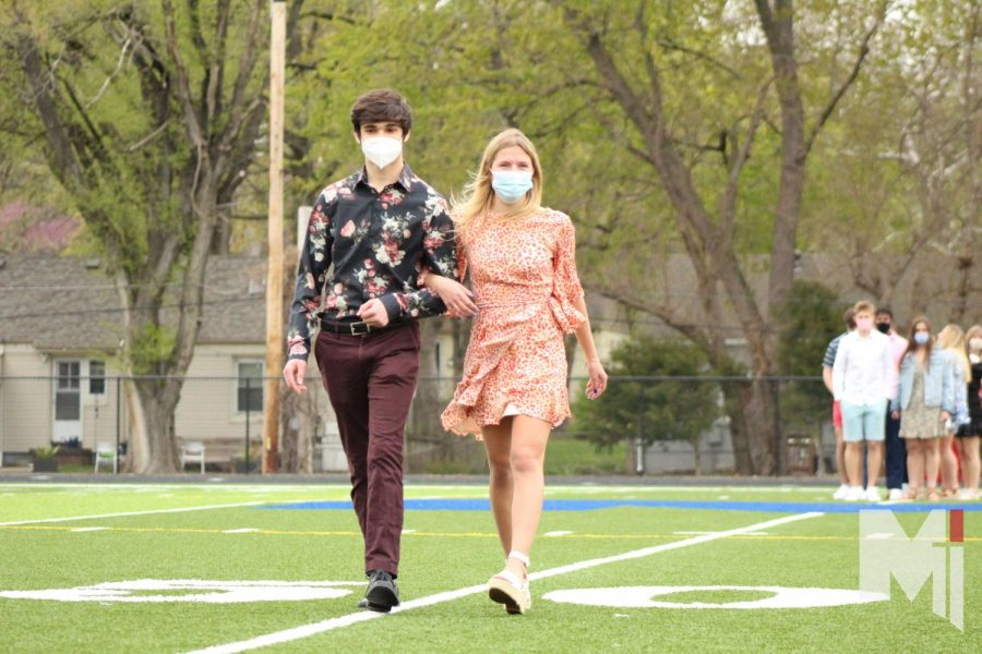 ANNOUNCING THE COURT  As senior Luke Attard and Mariel Allen's achievements echo throughout the stadium, students and teachers watch as they walk across the field. They were the first of the seven couples announced on April 23, herd day, for the prom court.