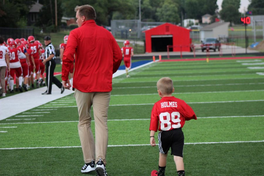 Walking on the field before the game, football coach Jon Holmes' son Hank Holmes follows his dad as he joins the team before the team's first home game kickoff. That night, the Stags took their first victory of the season with a final score of 23-20 against rival school Saint Thomas Aquinas.
